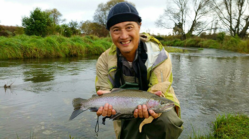 Lam holds a nice young maiden rainbow trout caught fly fishing while staying in Turangi beside the Tongariro river  at sportsman logde.